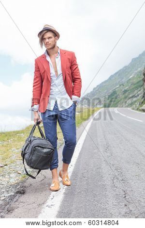 picture of a young fashion man posing outdoor, on the side of the road, with a hand in his pocket while holding a bag and looking away from the camera