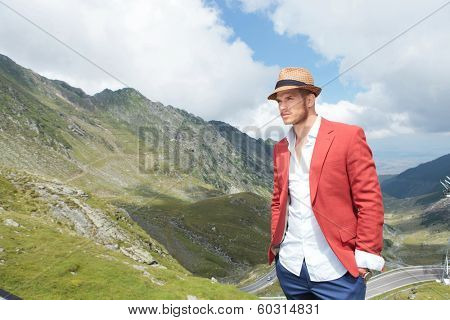 young fashion man posing outdoor, with both hands in his pockets while looking away from the camera, over a picturesque landscape
