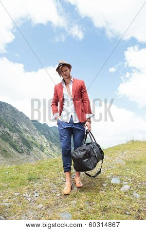 full length picture of a young fashion man walking in the mountains with a bag in his hand while looking into the camera