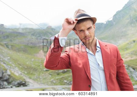 closeup picture of a young fashion man posing outdoor with his hand on his hat while looking into the camera