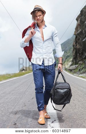 full length photo of a young fashion man walking down the middle of the road while holding his jacket over his shoulder and a bag in his hand