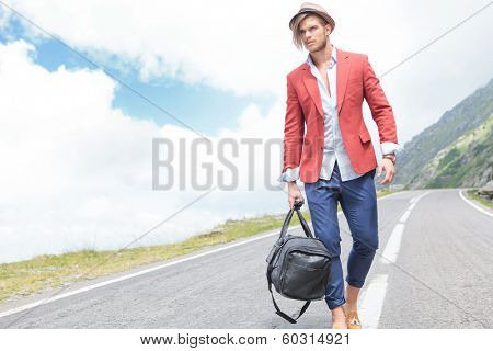 picture of a young fashion man strolling outdoor with a bag in his hand while looking away from the camera