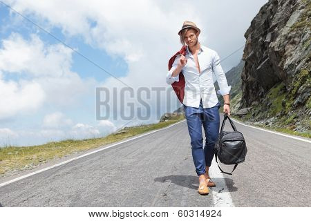 young fashion man walking down the road in the mountains, with his jacket over his shoulder and a bag in his hand, while looking into the camera