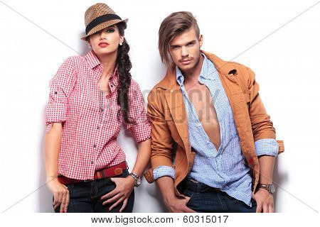 fashion young couple posing with hands in pockets against white studio wall