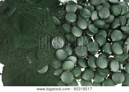 Spirulina powder and tablets algae nutritional supplement heap surface close up top view