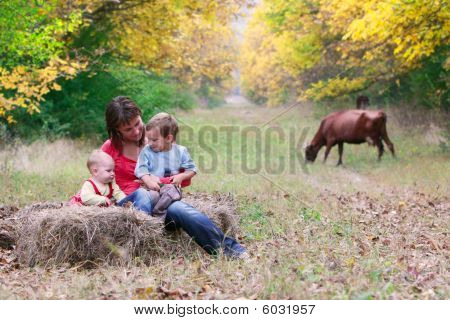 Happy Mother With Two Children In Autumn Park