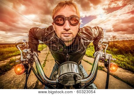 Funny Biker in sunglasses and leather jacket racing on the road (fisheye lens). Filter applied in post-production.