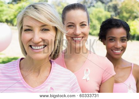 Portrait of confident female volunteers participating in breast cancer awareness