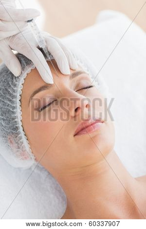 Closeup of beautiful woman recieving injection in forehead