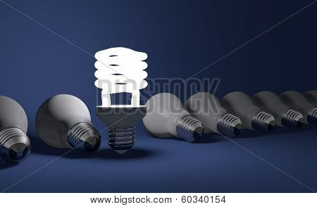 Standing Spiral Light Bulb In Row Of Lying Ones On Blue