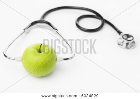 Green Apple Wearing Stethoscope Over White