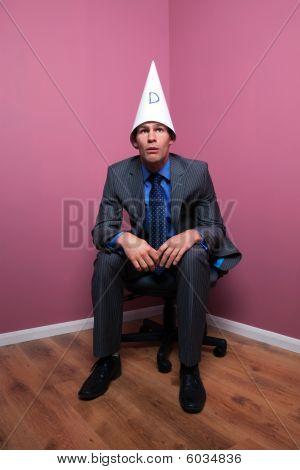 Businessman Sat In Corner Wearing Dunce Hat