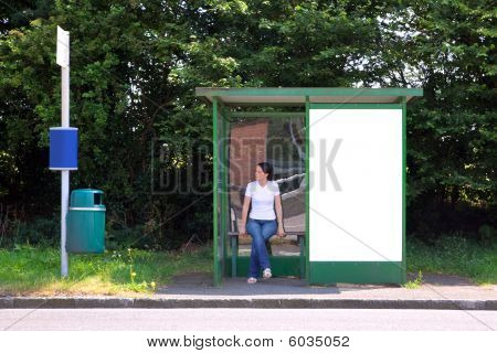 Woman Sat At A Bus Stop Next To Blank Billboard