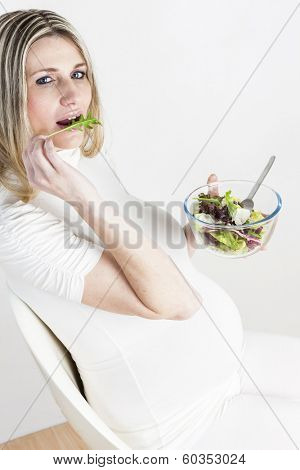 portrait of pregnant woman eating vegetable salad