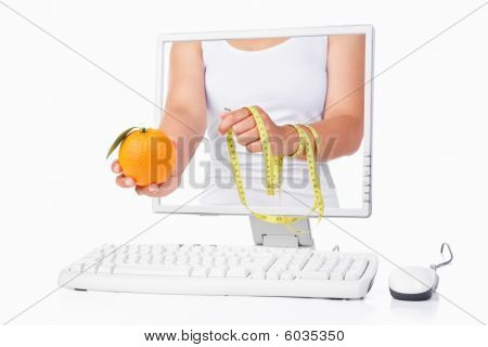 Female Hand Holding Orange And Measuring Tape Coming Out From Computer Screen