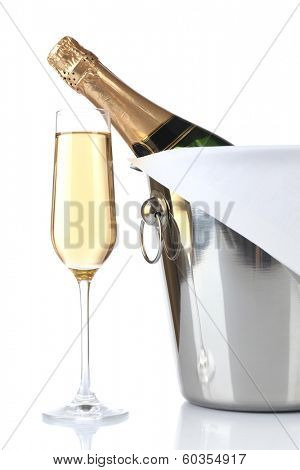Glass of champagne and bottle in pail, isolated on white