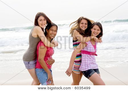 Teen girls piggyback on beach