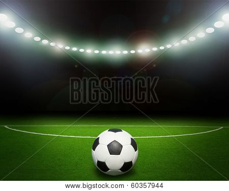 Green soccer field, bright spotlights, illuminated stadium
