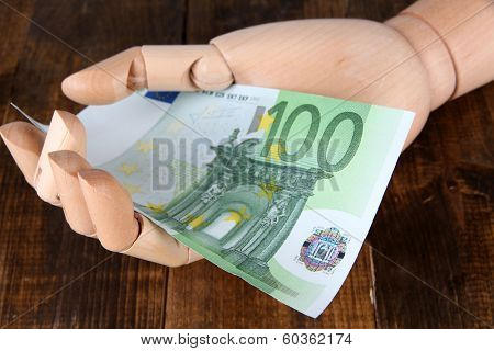 Money in wooden hand, on  color wooden background