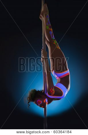 Elegant young pole dancer posing with UV makeup