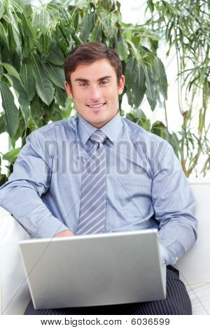 Businessman Using A Laptop On Couch And Smiling At The Camera