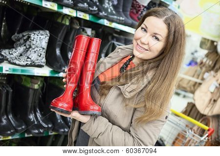 Young Woman Holding Red Watertights When Buying In Shop