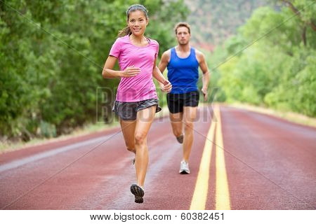 Athletes running - sport couple jogging in summer. Runners jogging in summer on road. Joggers training for marathon run. Fit male and female athletes in their 20s. Asian woman, Caucasian man.