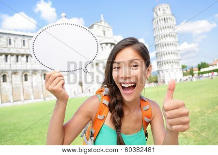 Travel tourist girl showing sign in Pisa, Italy. Young woman traveling holding speech bubble copy space with room for your text. Woman excited happy having fun in Pisa by Leaning Tower of Pisa, Italy.