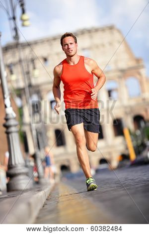 Runner - man running by Colosseum, Rome, Italy. Male athlete training for marathon jogging in city of Rome in front of Coliseum in full body length. Fit male sport fitness model jogger in run outside.