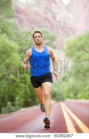 Runner - running athlete man. Male sprinting during outdoors training for marathon run. Athletic fit young sport fitness model in his twenties in full body length on road outside in nature.