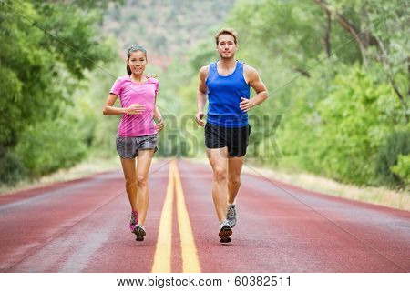 Fitness sport couple running jogging outside on road beautiful nature landscape. Runners training together for marathon run. Asian female sports woman and fit male fitness man in full body length.