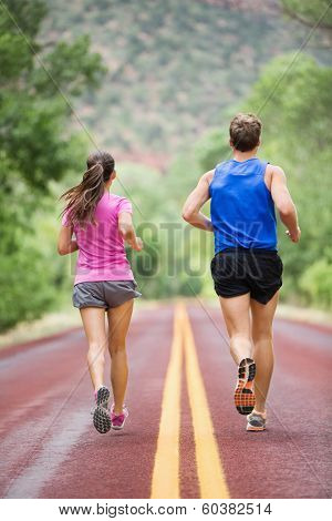 Running training runners jogging on road outside in rear view running away from camera in nature landscape. Sport fitness and healthy lifestyle concept with two people, man and woman.