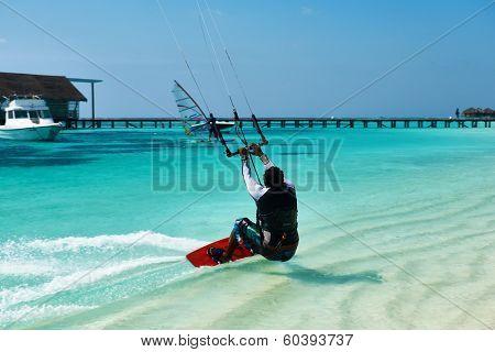 SOUTH ARI ATOLL, MALDIVES - DECEMBER 12 2013: Man kite surfing in waves