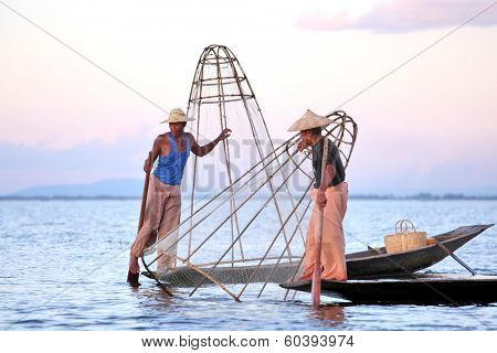 INLE LAKE, MYANMAR  DECEMBER 12, 2013: Fishermen at Inle Lake, Shan State, Myanmar Intha people possess the leg-rowing style and the unique coop-like fishing equipment