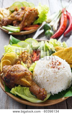 Famous traditional Malay food. Delicious nasi ayam penyet with sambal belacan. Local flavor. Fresh hot with steam smoke.