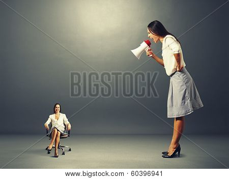 angry young woman screaming at smiley woman on the chair