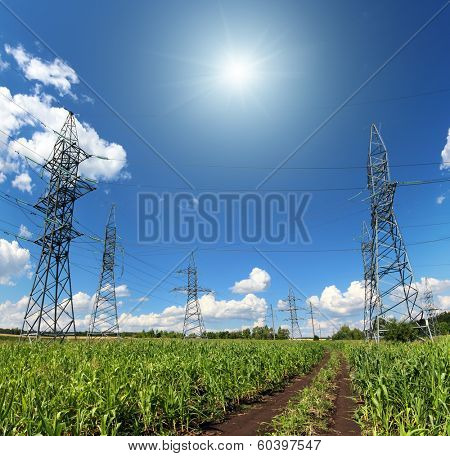 landscape with electric masts and road in green field