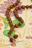 stock photo of prayer beads  - Islamic prayer beads over prayer rug under studio lighting - JPG