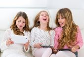picture of three sisters  - three kid sister friends girls group playing together with tablet pc on white sofa - JPG