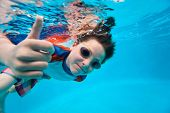 stock photo of swimming  - Cute little boy underwater in swimming pool - JPG