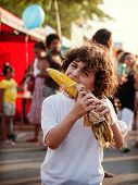 Hispanic Boy Eating Corn In A Street Festival