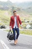 image of down jacket  - picture of a young fashion man walking on the middle of the road in the mountains while holding a bag in his hand and looking down - JPG