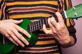 pic of ukulele  - Young Woman is Playing a green Ukulele - JPG