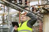 foto of substation  - Electrical Engineer with tablet PC in electrical substation - JPG