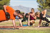 stock photo of boot camp  - Young woman working with adults in boot camp fitness class - JPG