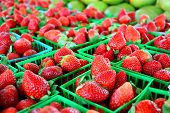 stock photo of strawberry  - a collection of fresh strawberries are gathered in baskets on a sale table at a farmer - JPG