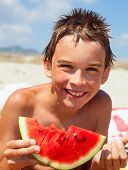 Happy boy eating watermelon on a beach