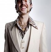 stock photo of gold tooth  - Portrait of a retro man with a gold tooth in a 1970s leisure suit and sunglasses smiling to the camera - JPG