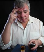 picture of bender  - Middle age man holding cordless phone atop Big Book of AA with filled shot glass nearby - JPG
