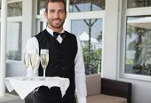 image of waiter  - Handsome smiling waiter holding tray of champagne in the patio of restaurant - JPG
